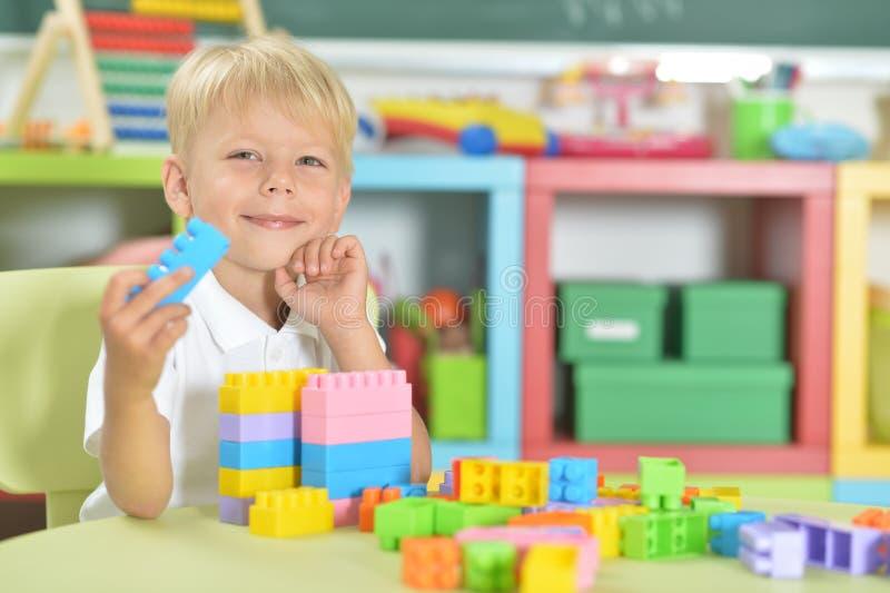 Retrato del muchacho lindo que juega con los bloques plásticos coloridos fotos de archivo