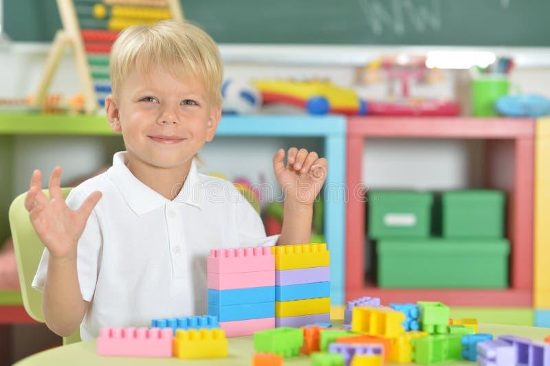 Retrato del muchacho lindo que juega con los bloques plásticos coloridos fotografía de archivo