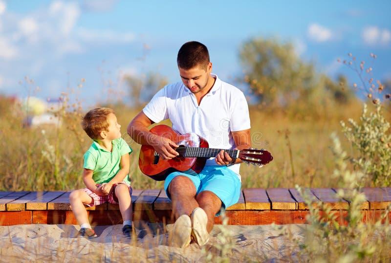 Retrato del muchacho lindo y de un hombre que toca una guitarra en campo del verano imagenes de archivo