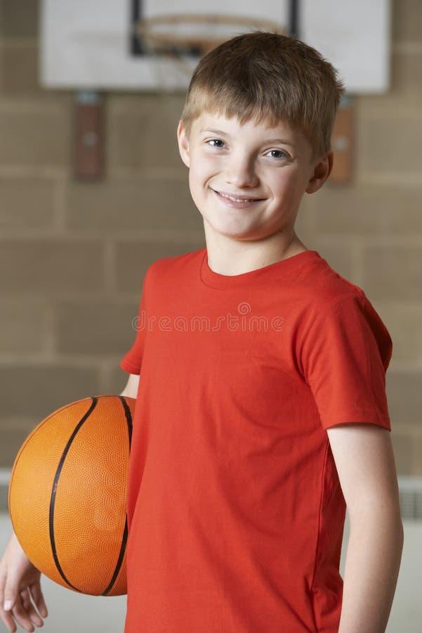 Retrato del muchacho que lleva a cabo baloncesto en gimnasio de la escuela imagen de archivo
