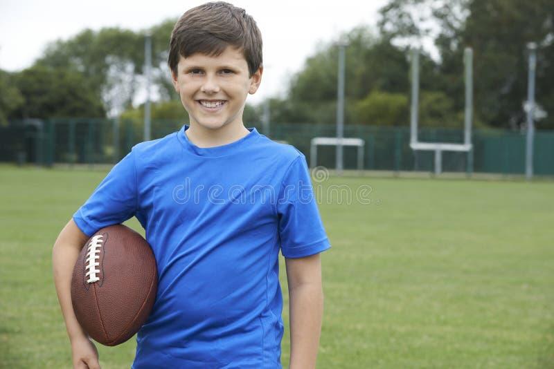 Retrato del muchacho que sostiene la bola en campo de fútbol de la escuela imagenes de archivo