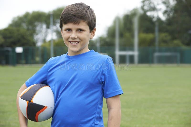 Retrato del muchacho que sostiene la bola en echada del rugbi de la escuela fotografía de archivo
