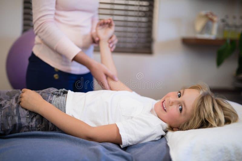 Retrato del muchacho sonriente que miente en cama mientras que brazo de examen del terapeuta de sexo femenino foto de archivo libre de regalías
