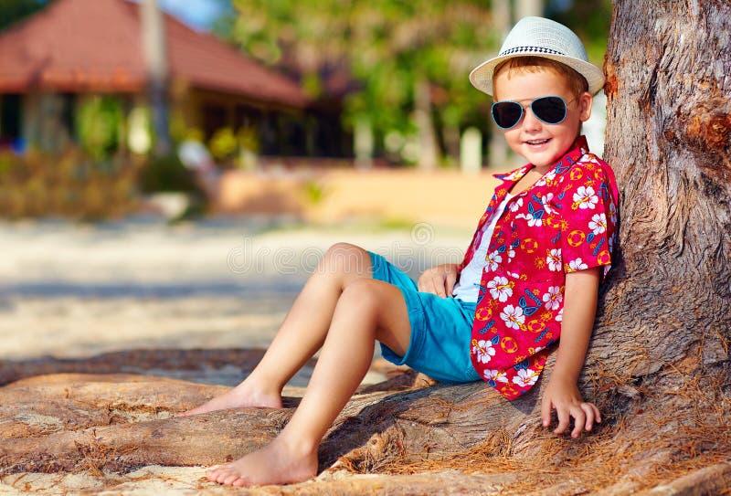 Retrato del muchacho sonriente que se sienta debajo del árbol fotografía de archivo libre de regalías