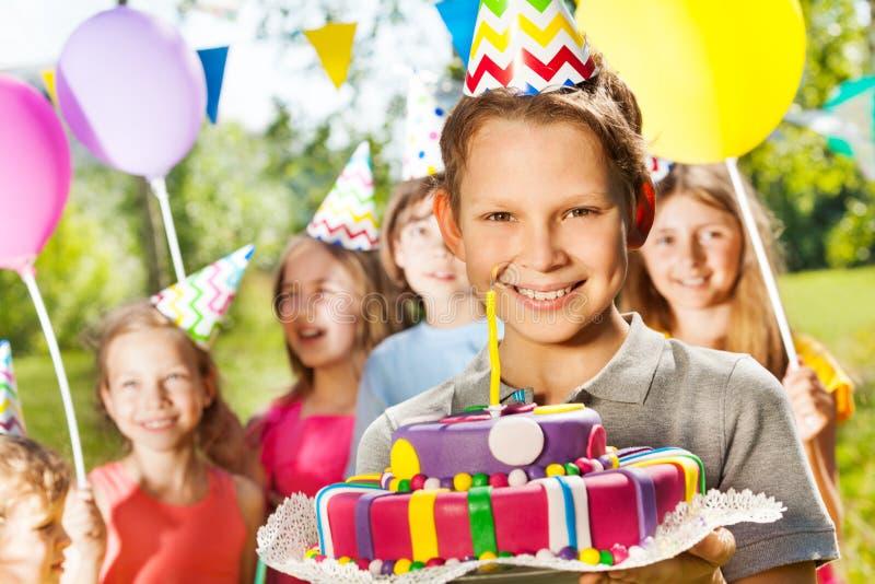 Retrato del muchacho sonriente que sostiene la torta de cumpleaños imagen de archivo