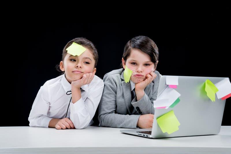 Retrato del muchacho y de la muchacha con las notas sobre las caras que se sientan en el lugar de trabajo imagenes de archivo