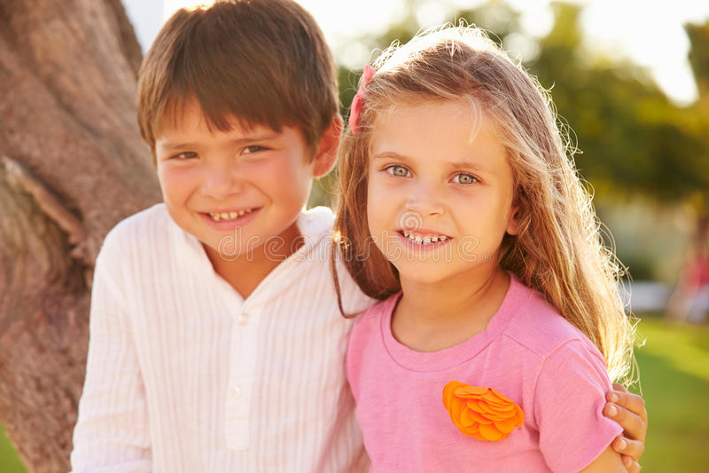 Retrato del muchacho y de la muchacha en parque junto imagen de archivo