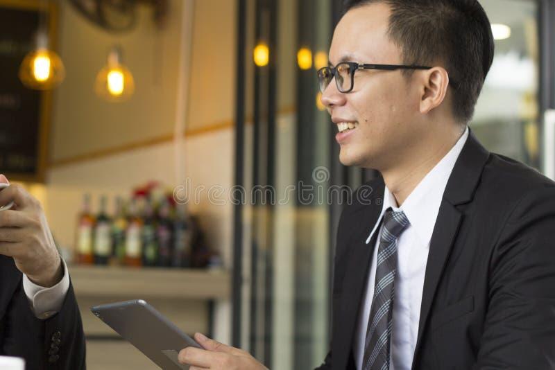 Retrato del negocio joven confiado que se sienta en la tabla en el encuentro al aire libre, llevando a cabo el informe de negocio fotos de archivo libres de regalías
