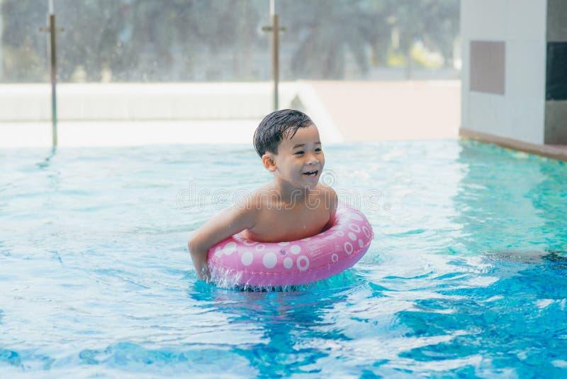 Retrato del niño asiático joven del niño del muchacho que ríe en una piscina Procedimiento de filtrado de la luz del sol fotos de archivo