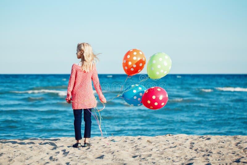 Retrato del niño caucásico blanco del niño del adolescente pensativo con el manojo colorido de globos, colocándose en la playa en fotografía de archivo