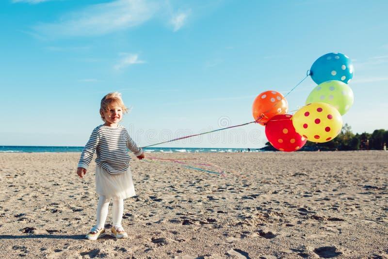 Retrato del niño caucásico blanco divertido del niño con el manojo colorido de globos, jugando la sonrisa en la playa en puesta d foto de archivo libre de regalías