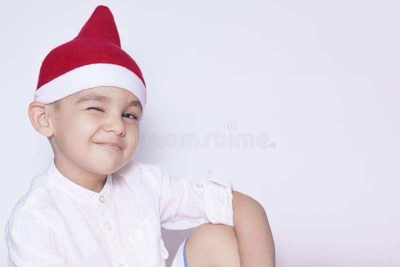 Retrato del niño de Oriente Medio de 6-7 años hermoso en el sombrero de Papá Noel Poco niño lindo que sonríe y que guiña Celebrac foto de archivo libre de regalías