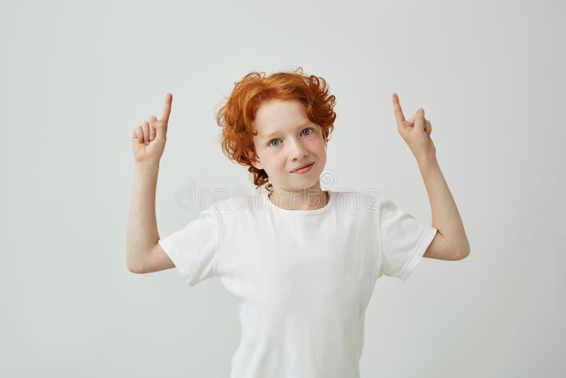 Retrato del niño divertido del jengibre con las pecas que señala la parte superior en la pared blanca con el espacio relajado de  fotos de archivo libres de regalías
