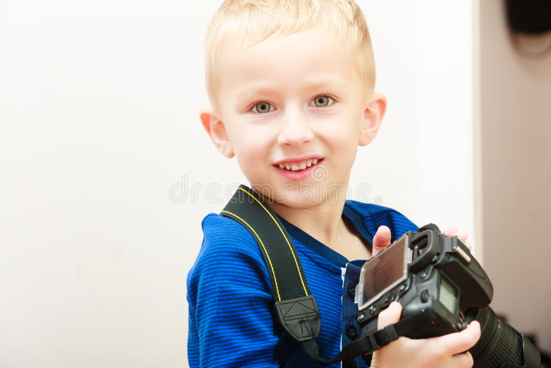 Retrato del niño feliz del niño del muchacho que juega con la cámara. En casa. foto de archivo