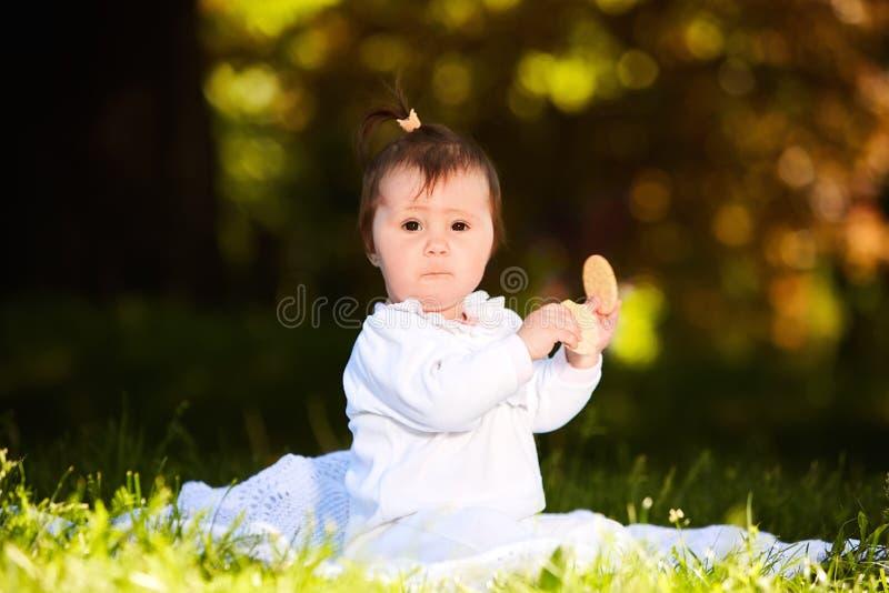 Retrato del niño feliz que se sienta en el prado y el bocado de los controles en el parque imagenes de archivo