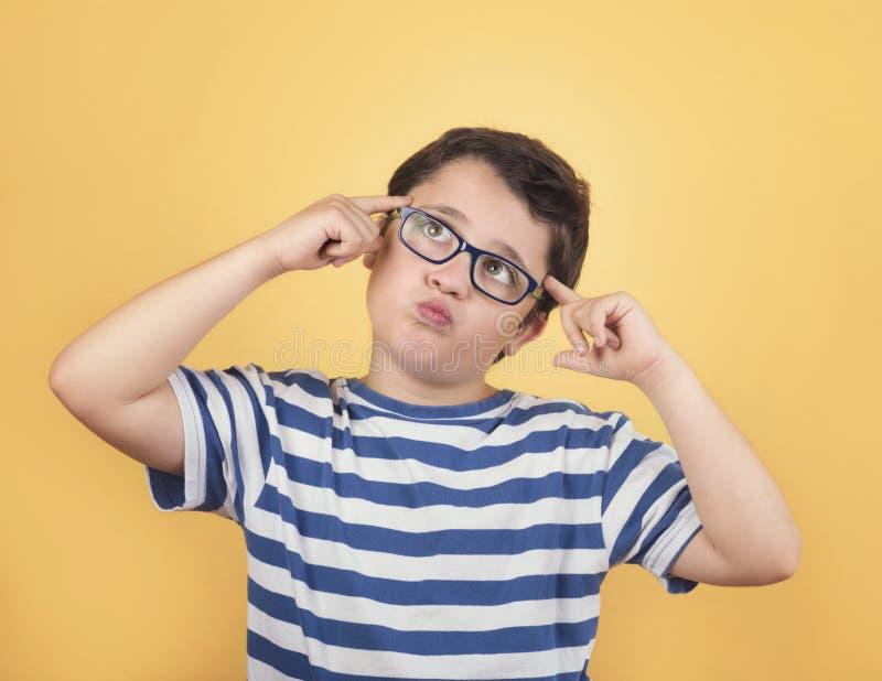 Retrato del niño pensativo con las lentes imagen de archivo libre de regalías
