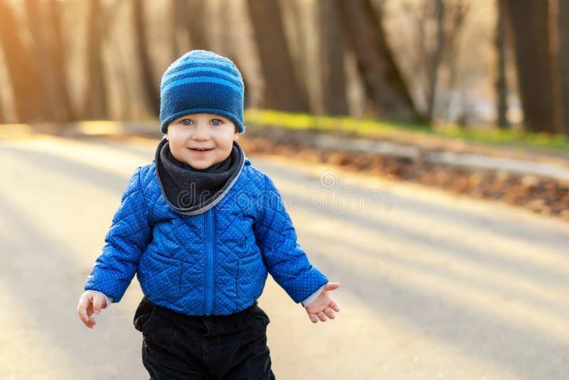Retrato del niño pequeño caucásico divertido lindo en chaqueta azul y sombrero que disfruta de caminar en el parque o el bosque d imagenes de archivo