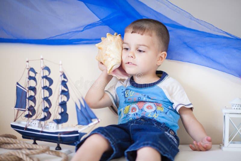 Retrato del niño pequeño caucásico lindo y feliz que escucha cuidadosamente una concha de berberecho grande fotos de archivo libres de regalías