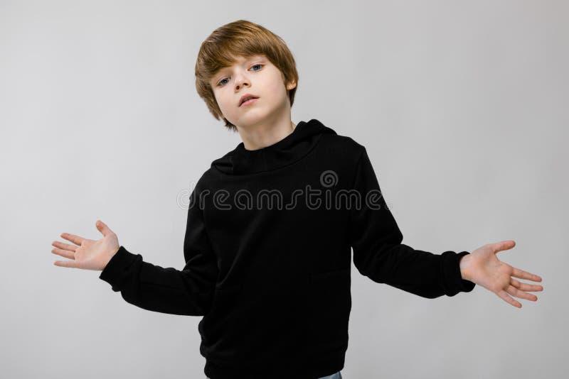 Retrato del niño pequeño confiado serio adorable con los brazos abiertos que se colocan en estudio en fondo gris foto de archivo