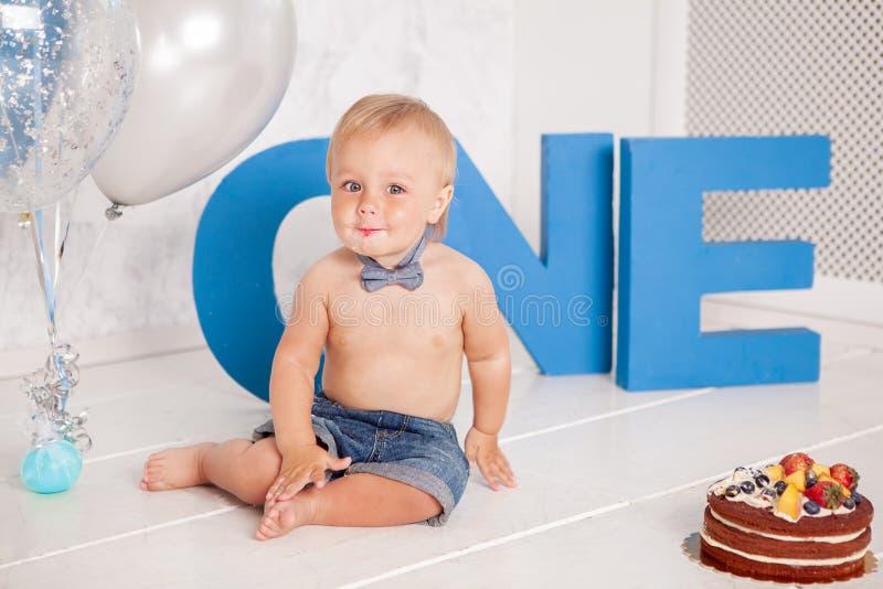 Retrato del niño pequeño divertido de la moda en estudio con las letras, los globos y la torta azules grandes fotos de archivo libres de regalías