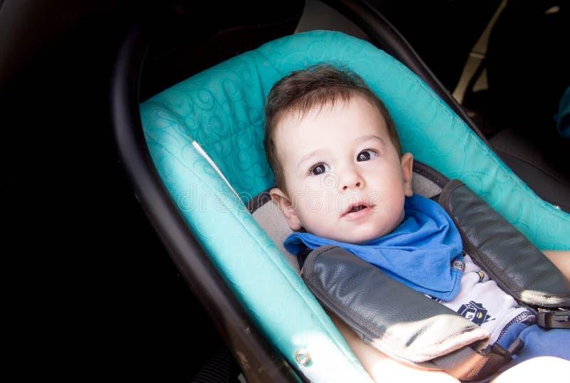 Retrato del niño pequeño en asiento de carro El pequeño niño sonriente del bebé sujetó con un retrato del cinturón de seguridad d foto de archivo