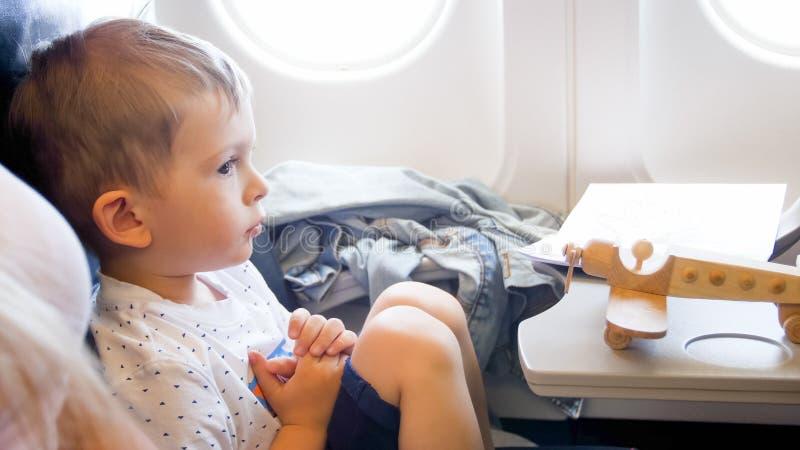 Retrato del niño pequeño lindo con la miniatura de madera del aeroplano durante vuelo largo imagen de archivo