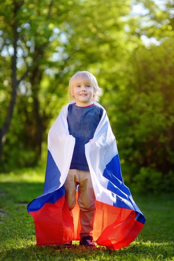 Retrato del niño pequeño lindo en parque público del verano con la bandera rusa en fondo Niño de las fans que apoya y que anima s foto de archivo