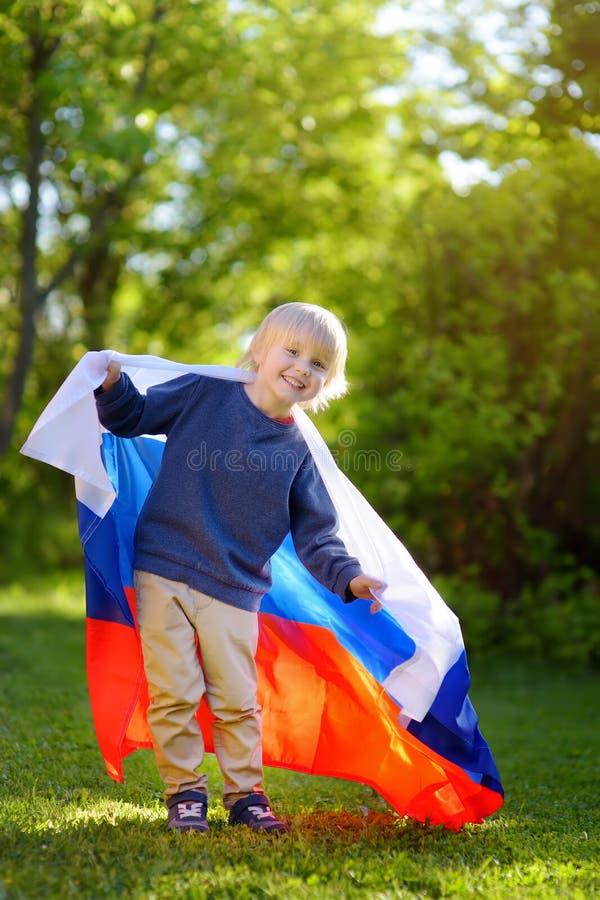 Retrato del niño pequeño lindo en parque público del verano con la bandera rusa en fondo Niño de las fans que apoya y que anima s foto de archivo libre de regalías