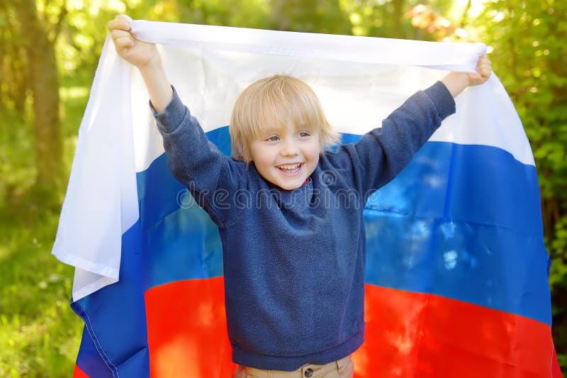 Retrato del niño pequeño lindo en parque público del verano con la bandera rusa en fondo Niño de las fans que apoya y que anima s fotografía de archivo