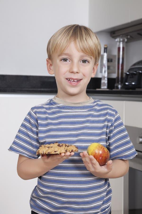 Retrato del niño pequeño lindo que elige entre la manzana y la galleta de microprocesador de chocolate imagen de archivo