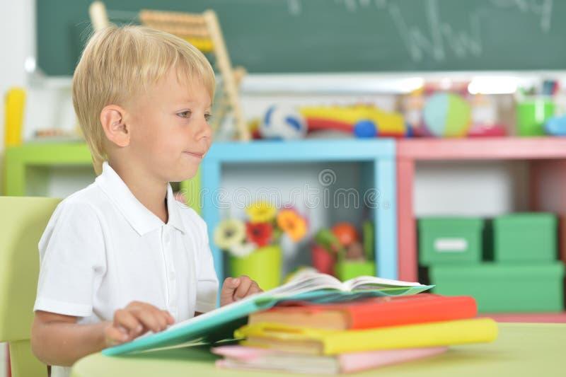 Retrato del niño pequeño lindo que hace la preparación en casa imagenes de archivo
