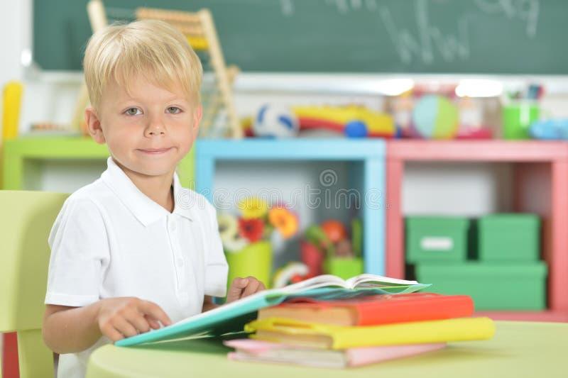 Retrato del niño pequeño lindo que hace la preparación en casa fotos de archivo libres de regalías