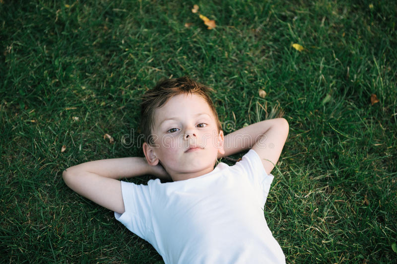 Retrato del niño pequeño lindo que miente en hierba verde foto de archivo