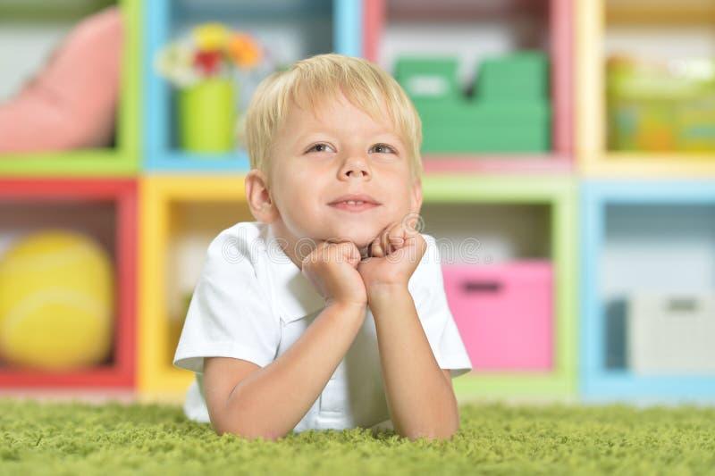 Retrato del niño pequeño lindo que miente en la alfombra verde foto de archivo