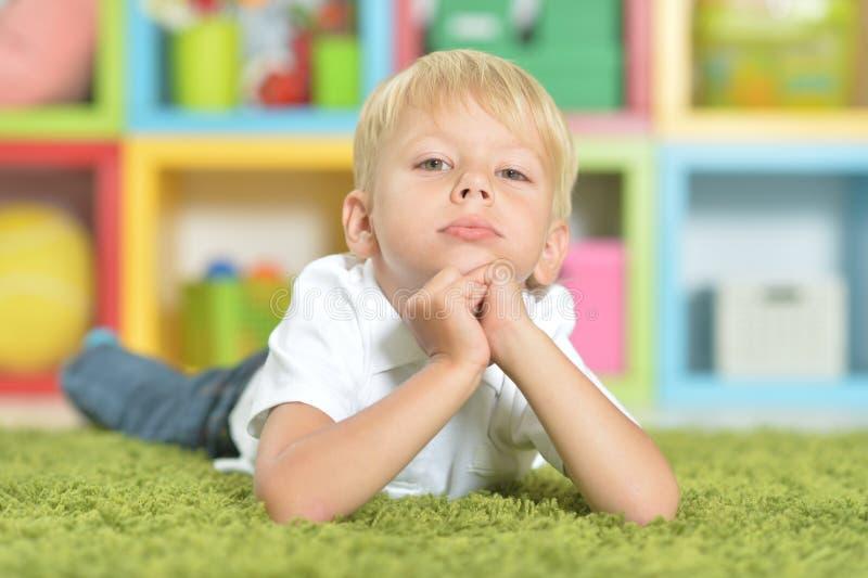 Retrato del niño pequeño rubio que miente en la alfombra verde foto de archivo libre de regalías