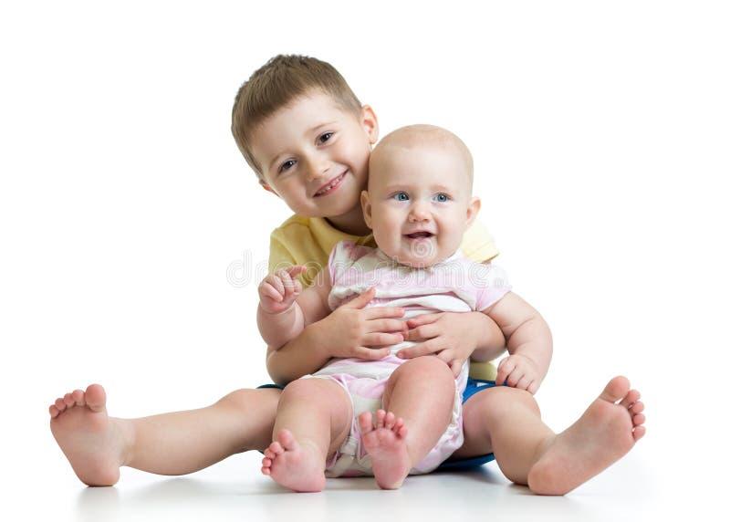 Retrato del niño que abraza a su pequeña hermana linda que se sienta en el piso aislado en el fondo blanco foto de archivo libre de regalías
