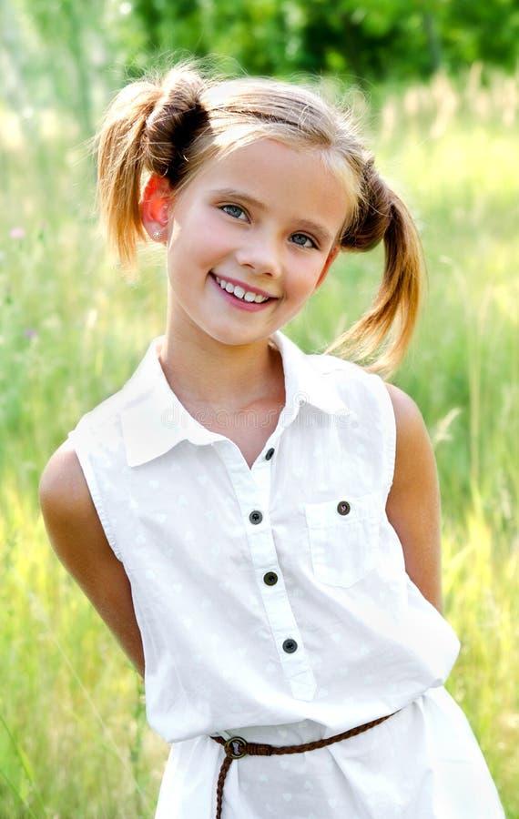 Retrato del niño sonriente adorable de la niña en el vestido al aire libre fotografía de archivo libre de regalías