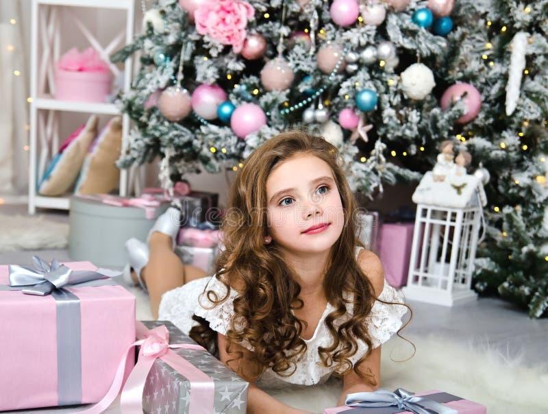 Retrato del niño sonriente feliz adorable de la niña en vestido de la princesa con las cajas de regalo que mienten cerca de árbol foto de archivo