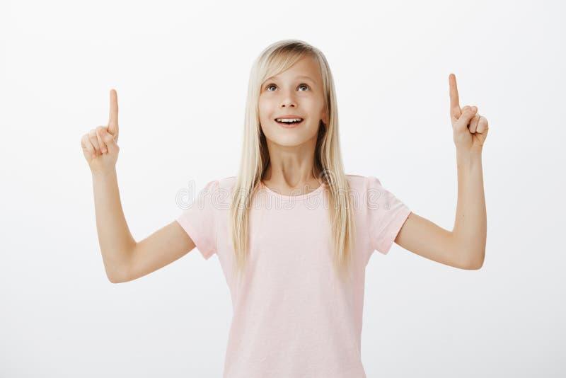 Retrato del niño sorprendente adorable con el pelo rubio en camiseta rosada, aumentando los dedos índices, destacando y mirando c fotografía de archivo