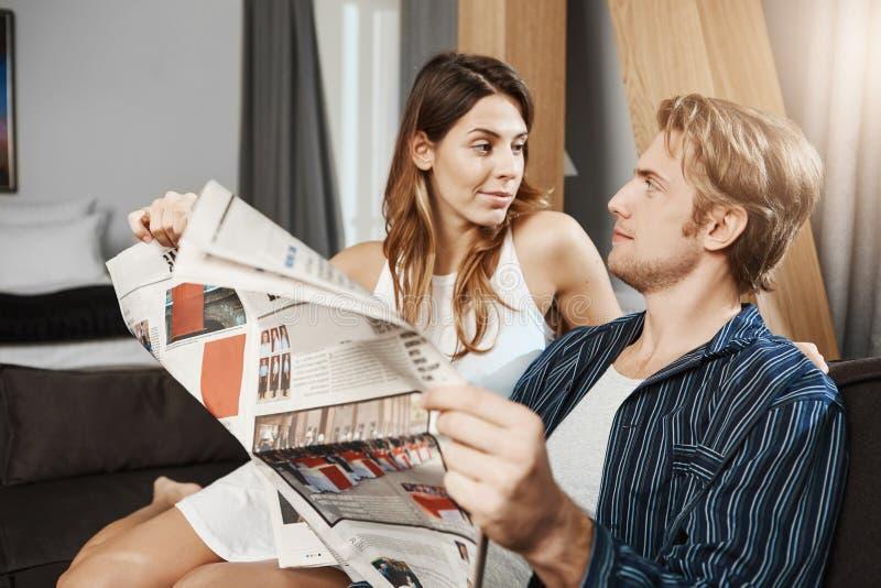 Retrato del novio barbudo hermoso que es distraído por la novia mientras que lee el periódico en casa La mujer quiere a fotografía de archivo