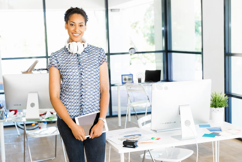 Retrato del oficinista afroamericano sonriente que se sienta en offfice imágenes de archivo libres de regalías