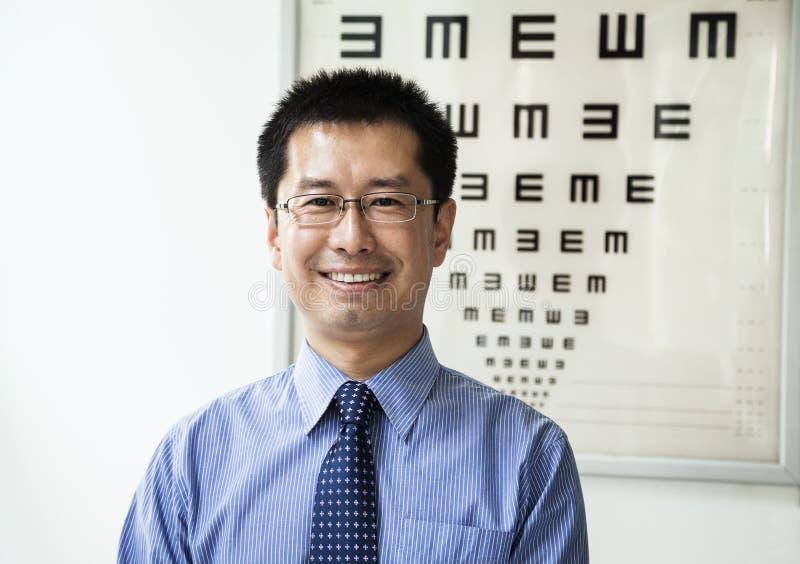 Retrato del optometrista sonriente con una carta de ojo en el fondo imagenes de archivo