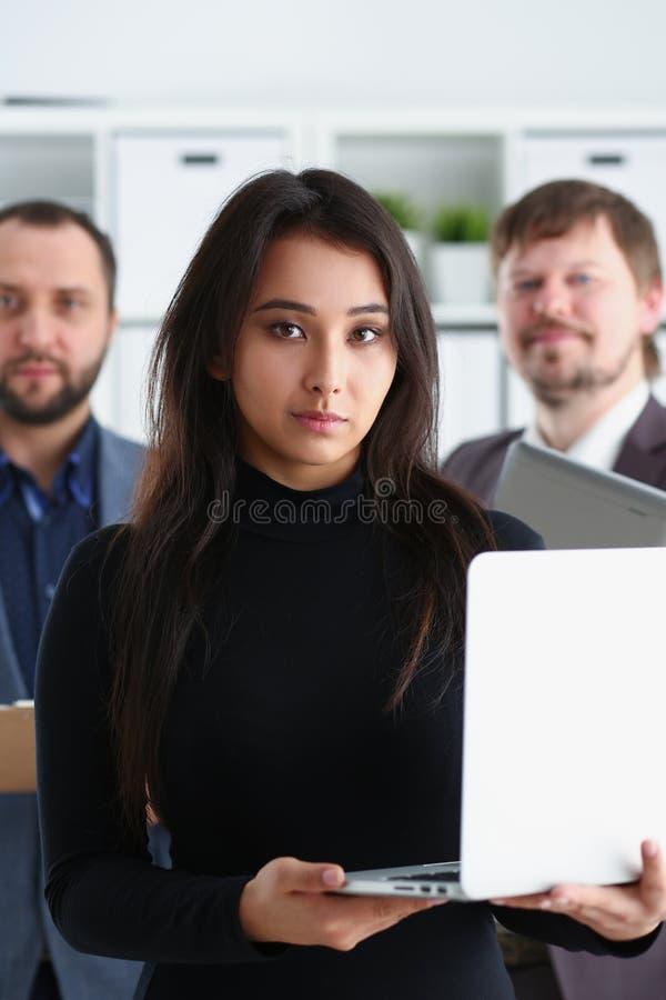 Retrato del ordenador portátil businesslady acertado joven del control y de dos hombres de negocios en oficina imagen de archivo