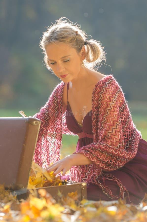 Retrato del otoño de la mujer bonita joven, con una baúl de viaje del vintage, fotos de archivo