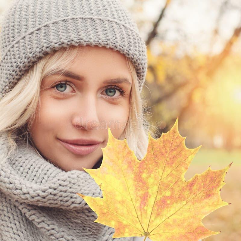 Retrato del otoño de la mujer joven con la hoja de arce otoñal al aire libre imagen de archivo libre de regalías