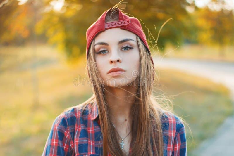 Retrato del otoño de una muchacha hermosa en una gorra de béisbol y un shir imagen de archivo libre de regalías