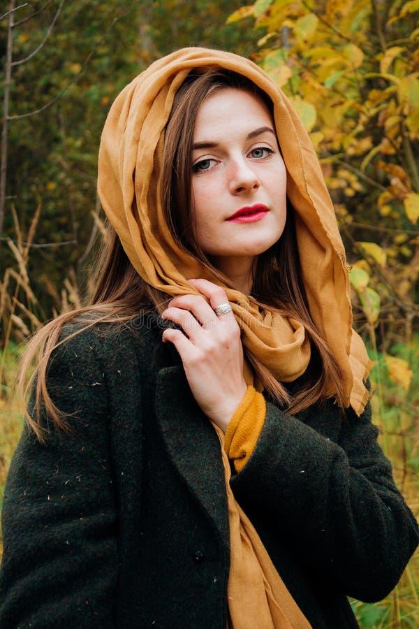 Retrato del otoño, muchacha hermosa joven con el pelo largo en naturaleza con la bufanda amarilla en su cabeza imagen de archivo