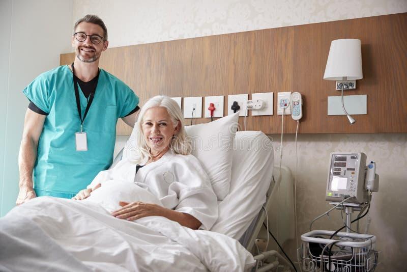Retrato del paciente de Visiting Mature Female del cirujano en cama de hospital fotografía de archivo