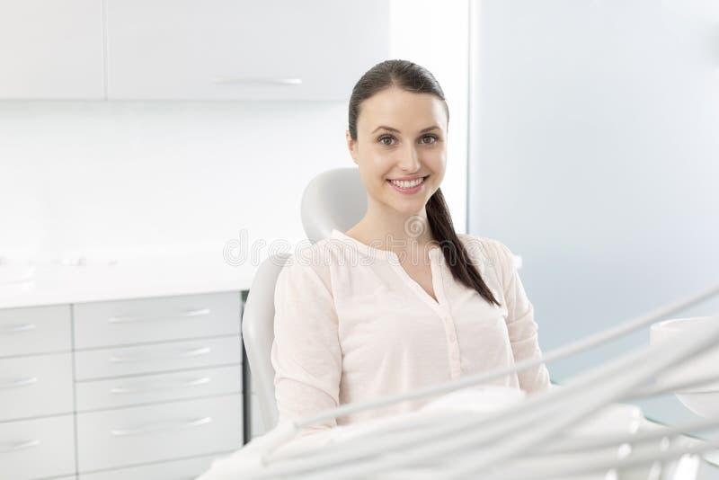 Retrato del paciente sonriente de la mujer que se sienta en silla en la clínica fotos de archivo libres de regalías
