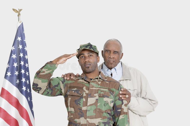 Retrato del padre con el soldado de los E.E.U.U. Marine Corps que saluda la bandera americana sobre fondo gris imagenes de archivo